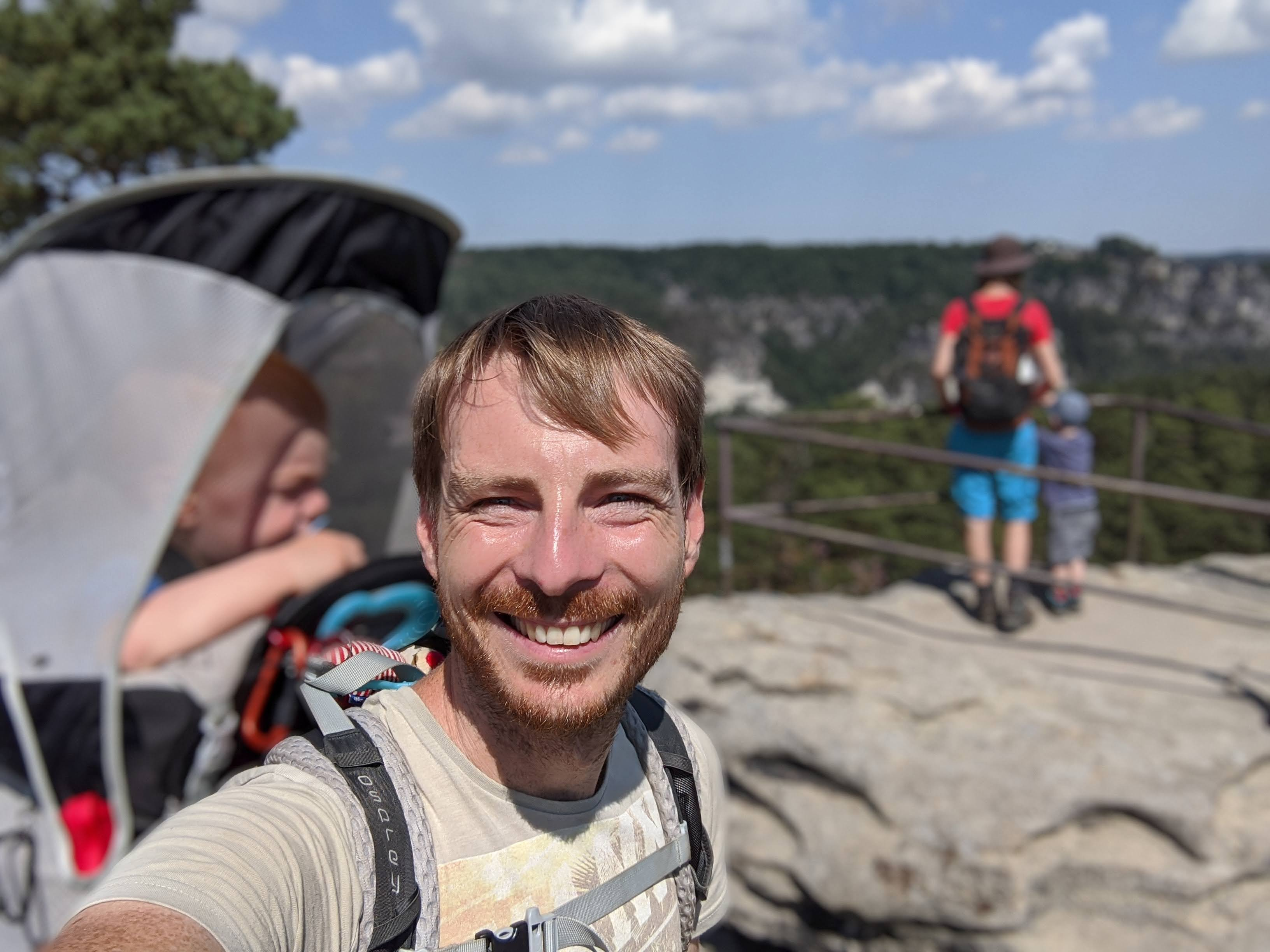 Familie beim Wandern mit Kraxe und Rucksack